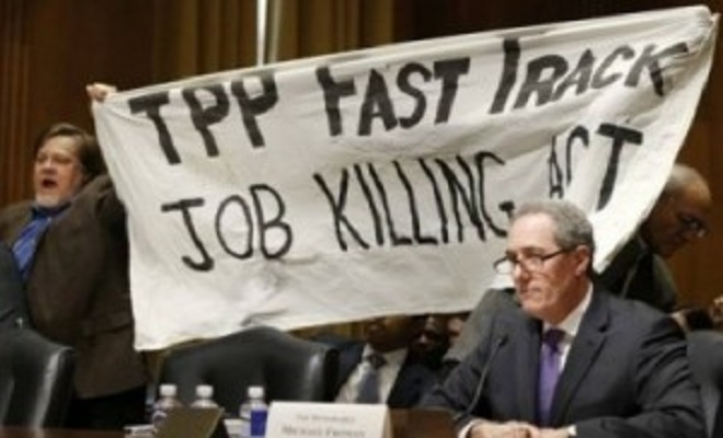 CorbettReportTPP-Protest-Froman-miffed-as-KZ-and-Dick-Ochs-hold-banner-behind-him.-Source-Reuters.-e1429808714476-300x193